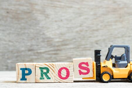 Toy forklift hold letter block to complete word pros on wood background Imagens