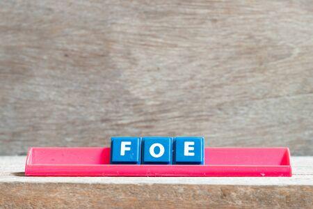 Tile letter on red rack in word foe on wood background 版權商用圖片