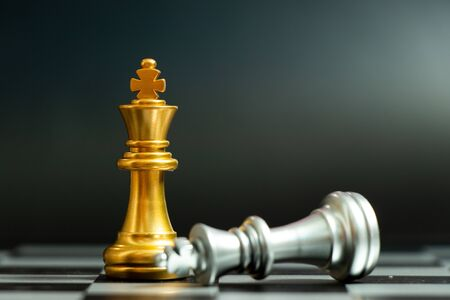 Gold king chess piece win over lying down silver king on black background