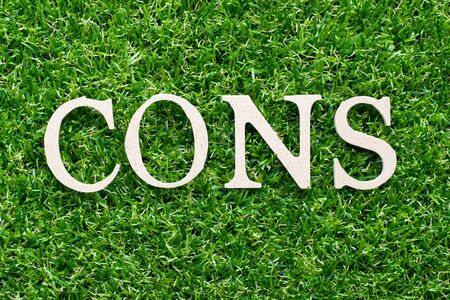 Wood alphabet in word cons on artificial green grass background
