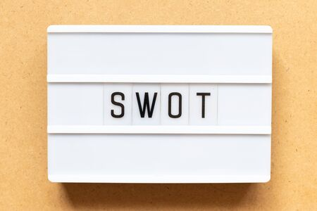Lightbox with word swot (abbreviation of strength, weakness, opportunities, threats) on wood background
