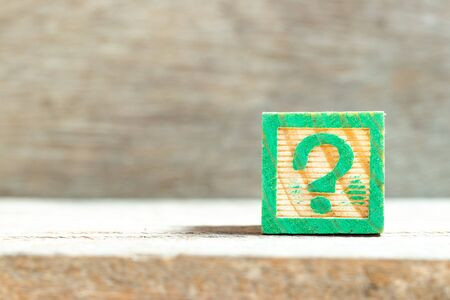 Color letter block in question mark sign on wood background Stock Photo