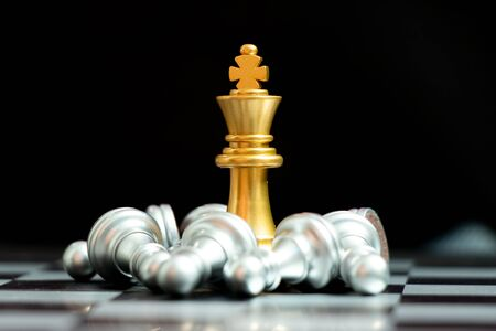 Gold king chess piece win over lying down pawn on black background (Concept for leadership, crisis management)