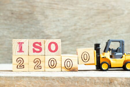 Toy forklift hold letter block to complete word iso 22000 on wood background