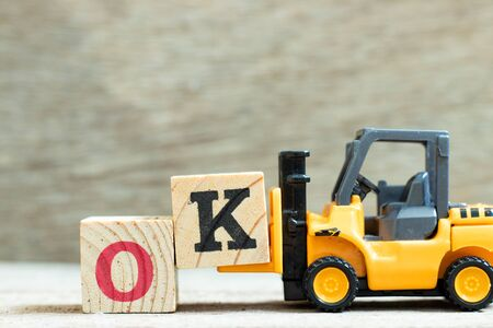 Toy forklift hold letter block K to complete word OK on wood background