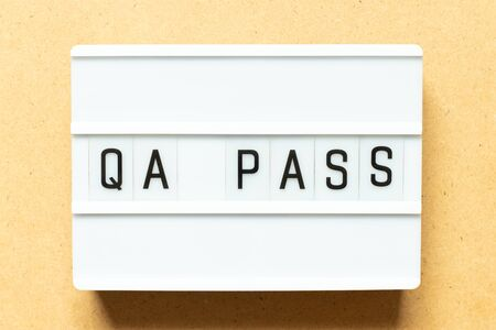 Lightbox with word QA (Abbreviation of Quality Assurance) pass on wood background