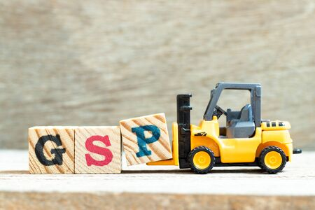 Toy forklift hold letter block P to complete word GSP (Abbreviation of Good Storage Practice or Generalized System of Preferences or Gross State Product) on wood background Archivio Fotografico - 149593151