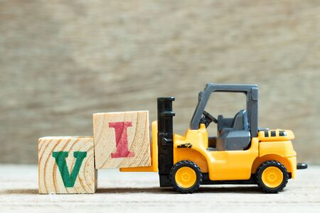 Toy forklift hold letter block to complete word VI (abbreviation for value investor) on wood background