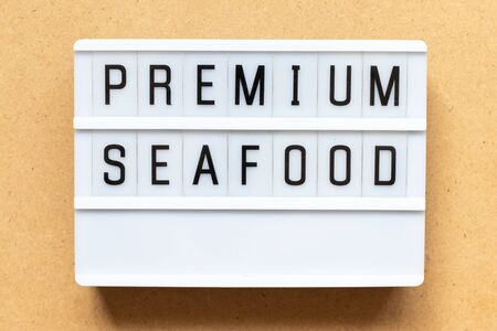 Lightbox with word premium seafood on wood background