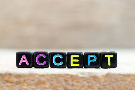 Black bead with color letter in word accept on wood background Stok Fotoğraf