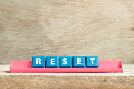 Tile letter on red rack in word reset on wood background