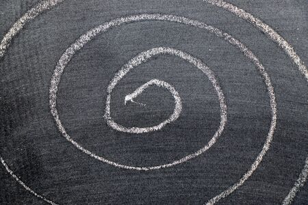 White color chalk hand drawing in spiral shape on black board background