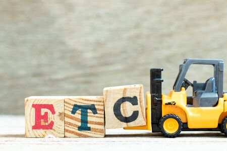 Toy forklift hold letter block c to complete word etc (abbreviation of et cetera) on wood background