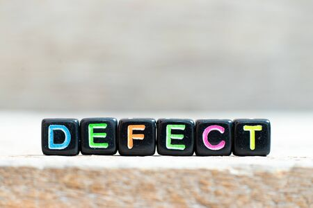 Black bead with color letter in word defect on wood background