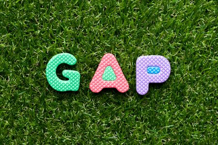Toy foam letter in word GAP (abbreviation of good agricultural practice) on green grass background