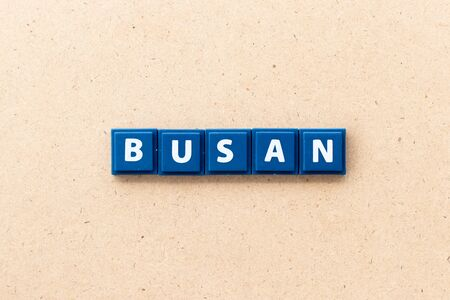 Tile letter in word Busan on wood background 写真素材