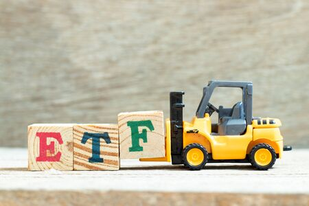 Toy forklift hold letter block to complete word ETF (abbreviation of Exchange Traded Fund) on wood background