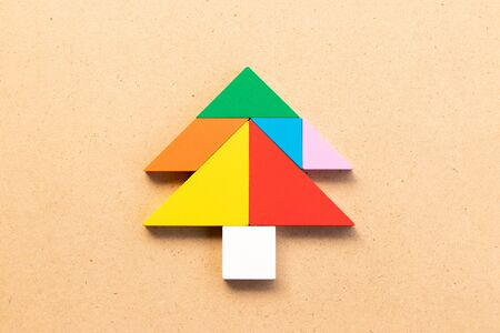 Color tangram puzzle in pine or christmas tree shape on wood bacground Archivio Fotografico