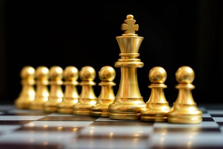 Gold king chess piece stand with pawn on black background (Concept of teamwork, management)