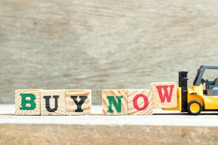 Toy forklift hold letter block w to complete word buy now on wood background Stockfoto