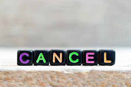 Black bead with color letter in word cancel on wood background