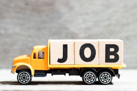 Truck hold letter block in word job on wood background Archivio Fotografico