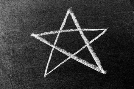 White color chalk hand drawing in star shape on black board background Archivio Fotografico