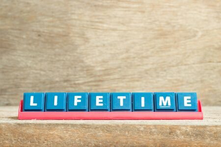 Tile letter on red rack in word lifetime on wood background