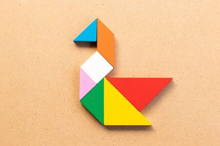 Color tangram puzzle in swan or duck shape on wood bacground