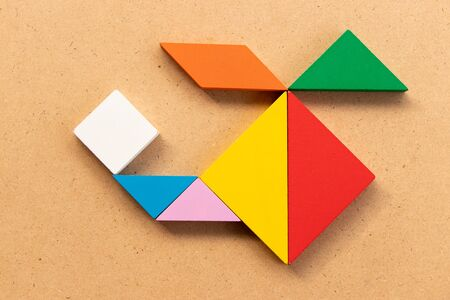 Color tangram puzzle in copter or helicopter shape on wood bacground
