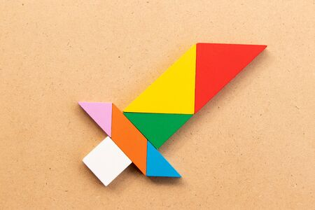 Color tangram puzzle in sword shape on wood bacground