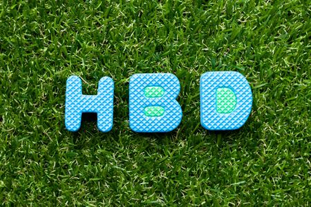 Toy foam letter in word HBD (Abbreviation of happy birthday)  on green grass background