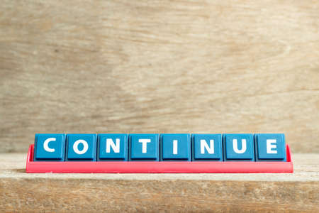 Tile letter on red rack in word continue on wood background