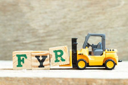 Toy forklift hold letter block R to complete word FYR (abbreviation of for your reference) on wood background Archivio Fotografico