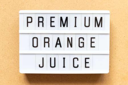 Lightbox with word premium orange juice on wood background
