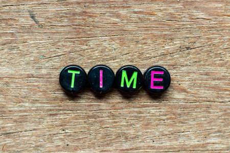 Black bead with color letter in word time on wood background