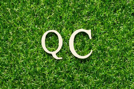 Wood alphabet letter in word QC (Abbreviation of Quality Control) on green grass background