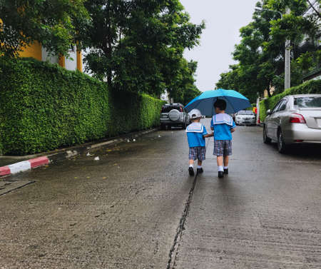 Two student brothers walking in the rain with umbrella.