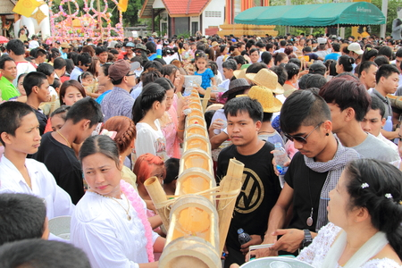 sangkhla buri: KANCHANABURI ,THAILAND - APRIL 17:The unidentified people pour the water into the bamboo rails to water a monk in Songkran festival on April 17, 2014 in Sangkhla Buri, Kanchanaburi , Thailand.