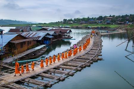 sangkhla buri: KANCHANABURI ,THAILAND - APRIL 18 2014: Buddhist monks walk on Bamboo Bridge the Sangkhla Buri River, Kanchanaburi, Thailand. Editorial