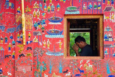 prying: LUANG PRABANG LAOS  JUNE 9 2015 : tourist is prying for Buddha at wat Xieng Thong in Luang Prabang  Laos
