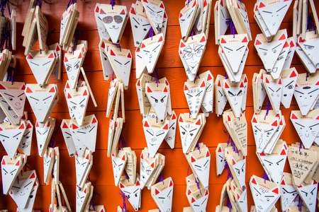 ema: KYOTO, JAPAN - MARCH 24, 2016 : Ema prayer tables with unique fox-shaped boards at Fushimi Inari Taisha Temple in Kyoto. Pray for luck, wealth, happiness, health, fortune, protection. Editorial