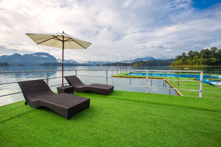 Lake view in summer with relaxation seat and umbrella in wooden terrace at Thailand Summer Season Stock Photo