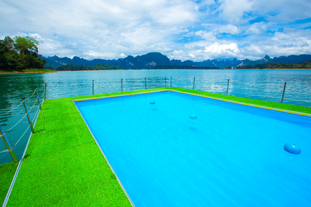 Tropical resort. Poolside with beautiful lake view Stock Photo