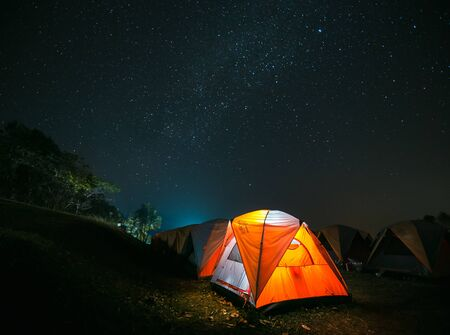 Traveling and camping concept - camp tent at night under a sky full of stars. Zdjęcie Seryjne