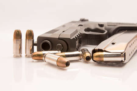 full jacket bullet: close-up on 9mm ammo with a handgun.