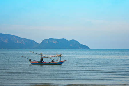 a fishing boat on the sea with blue sky