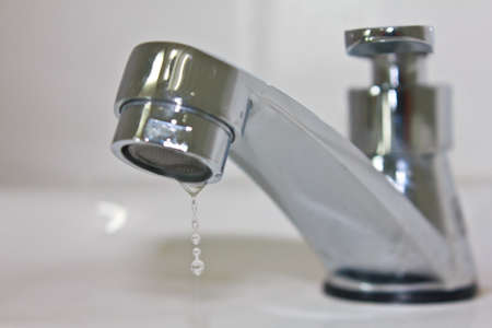 Primer grifo moderna con una gota de agua Foto de archivo