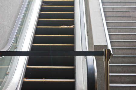 Broken old escalator with black stop tap