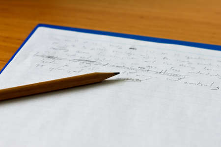 A wood pencil and old notepad paper on the table photo